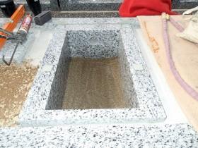 御影石納骨室の中に洗い砂をひきます