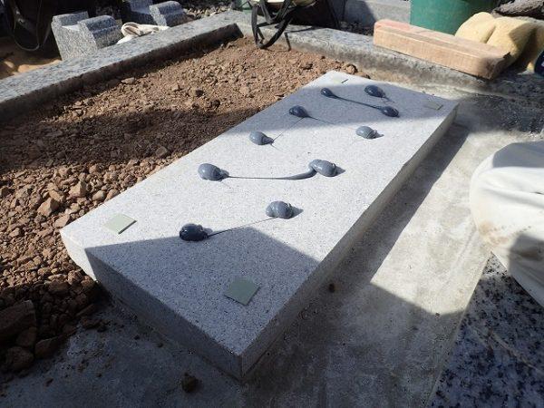 墓誌の補強石の上に免震シリコン+免震接着剤施工で地震対策施工をして墓誌を組みます
