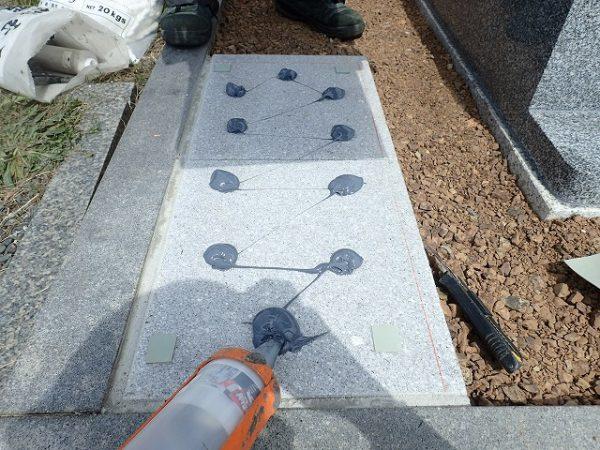墓誌の補強石の上に耐震接着剤