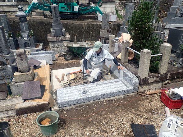 強化モルタルで外柵基礎石を一本ずつ丁寧に組みます