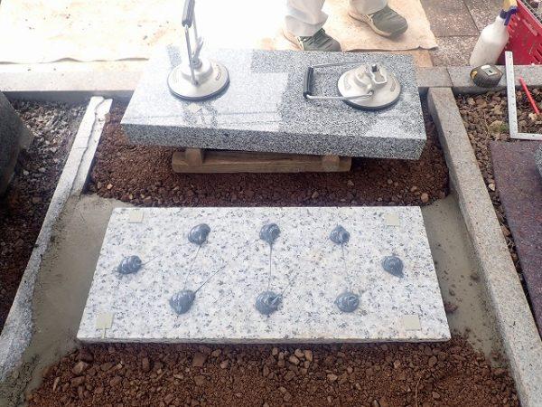 墓誌の補強石の上に、耐震接着剤を使って施工します