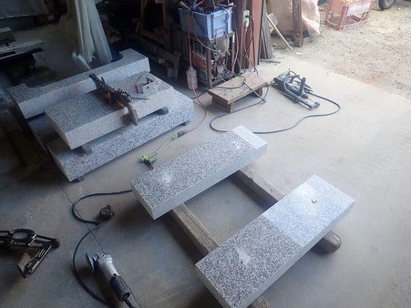 工場で作った外柵基礎石に金具を取り着けます